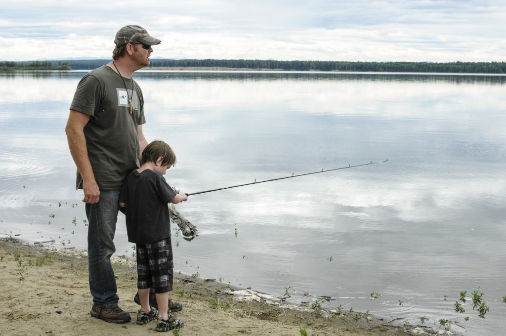 Dad teaching child to fish