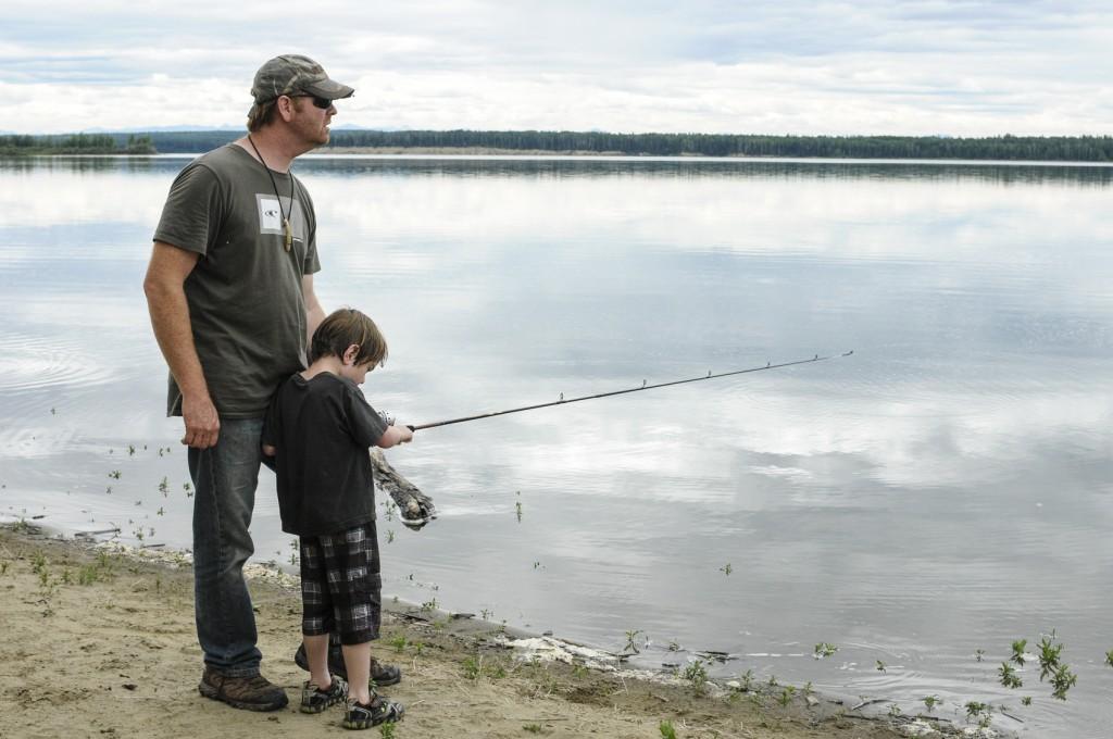 Dad teaching child to fish