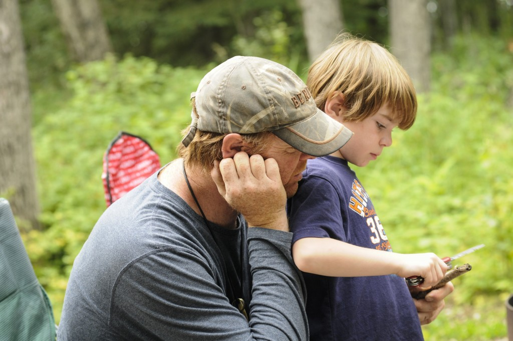 Dad teaching child to whittle