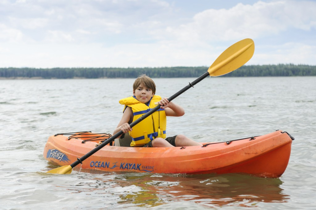 child kayaking on lake