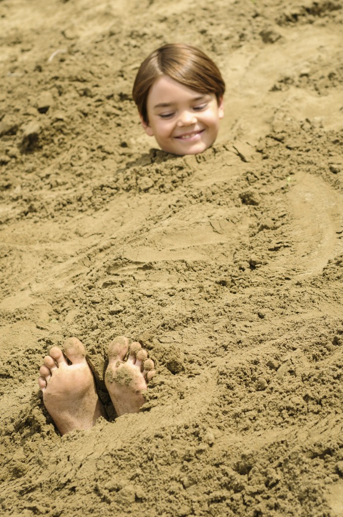 child buried in the sand at beach