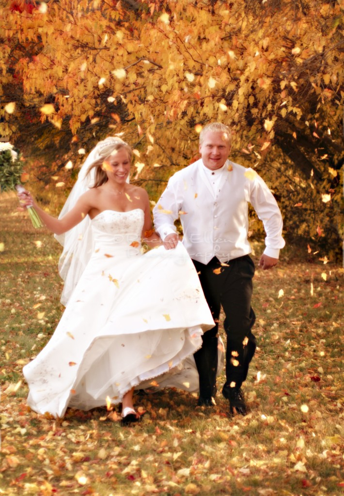 bride and groom running through fall leaves